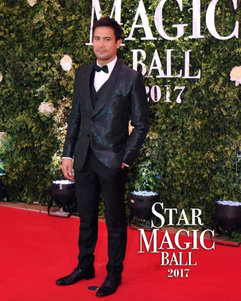 Sam Milby in a jacquard jacket and black trousers.